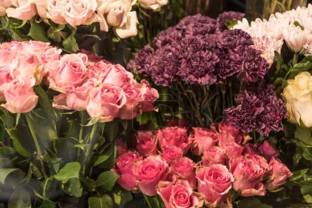 beautiful pink and burgundy roses and carnation flowers at flower shop
