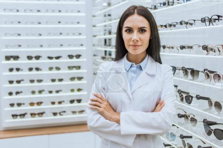 professional optometrist with crossed arms posing near shelves with eyesight in optica