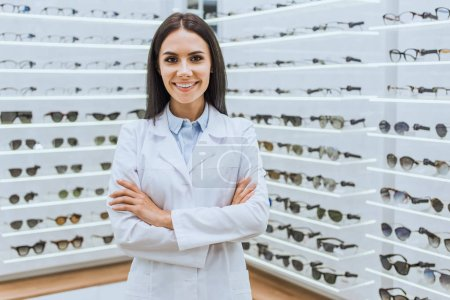 professional smiling optometrist posing with crossed arms near shelves with eyesight in optica