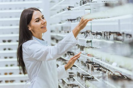 professional smiling optician taking glasses from shelves in ophthalmology