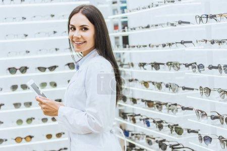 Photo pour Opticien attrayant à l'aide de tablette numérique à le œuvre dans la boutique ophtalmique - image libre de droit