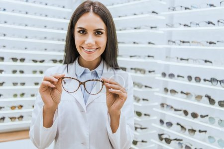 Photo for Professional smiling optometrist holding glasses in ophthalmic shop - Royalty Free Image