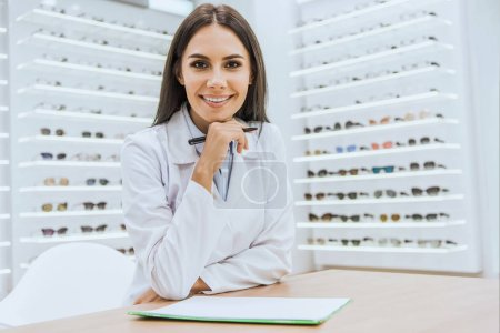 Photo for Smiling optician with papers and pen looking at camera in ophthalmology - Royalty Free Image