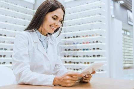 Photo for Professional smiling optician using tablet in optica - Royalty Free Image