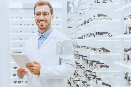 Photo for Professional smiling optometrist using digital tablet near eyeglasses on shelves in ophthalmic shop - Royalty Free Image