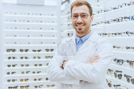 Photo for Portrait of smiling professional optometrist in glasses posing with crossed arms in optica - Royalty Free Image