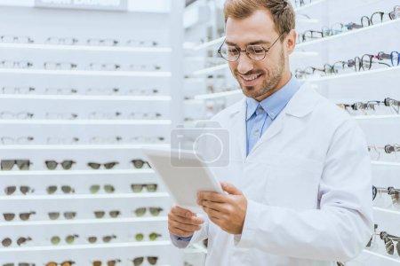 Photo pour Souriant opticien mâle à l'aide de tablette numérique dans optica avec lunettes sur les tablettes - image libre de droit
