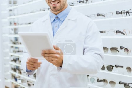 Photo for Cropped view of optometrist in white coat using digital tablet in optica - Royalty Free Image