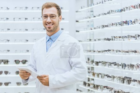 smiling male optometrist using tablet in optica with eyesight on shelves