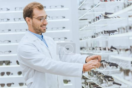 smiling oculist taking eyesight from shelves in ophthalmic shop