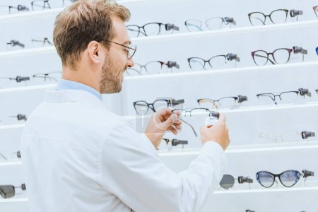 oculist taking eyeglasses from shelves in ophthalmic shop