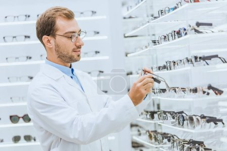 professional male oculist taking eyeglasses from shelves in ophthalmic shop
