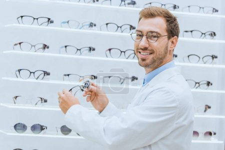 smiling doctor in white coat taking eyeglasses from shelves in optica