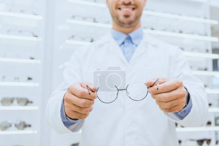 cropped view of optician in white coat holding glasses, selective focus