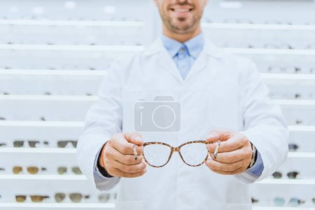 Photo for Cropped view of oculist in white coat holding eyeglasses, selective focus - Royalty Free Image