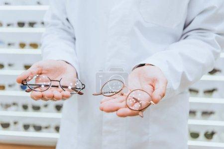 partial view of professional doctor in white coat holding glasses