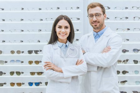 professional smiling oculists posing with crossed arms in ophthalmic shop with glasses