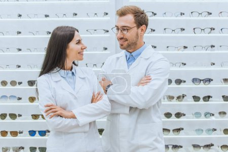 happy professional opticians in white coats posing with crossed arms in ophthalmology
