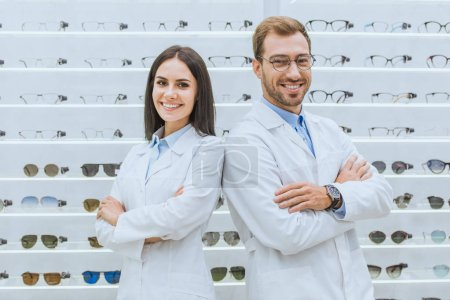 professional opticians posing with crossed arms in ophthalmic shop with glasses