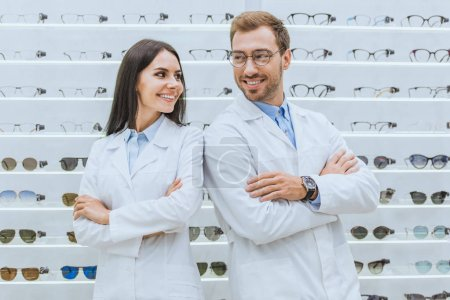 professional smiling oculists standing with crossed arms in ophthalmology