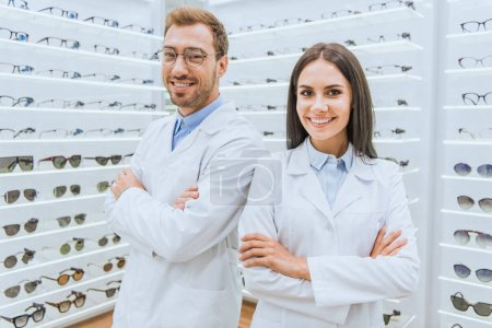 professional opticians in white coats standing with crossed arms in ophthalmology