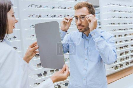 side view of female optometrist holding mirror while man choosing eyeglasses in optica