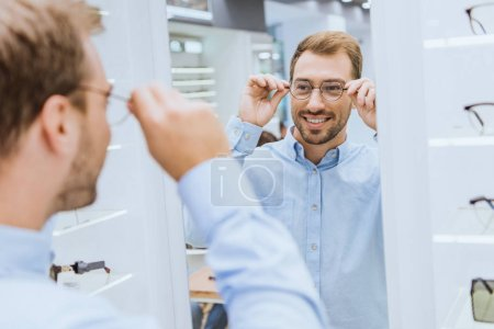 partial view of smiling young man choosing eyeglasses and looking at mirror in optica