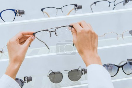 Photo for Cropped view of doctor taking eyeglasses from shelf in ophthalmic shop - Royalty Free Image