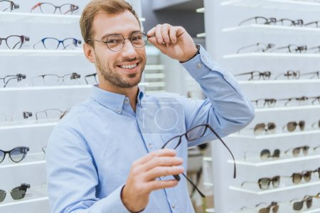 cheerful young man choosing eyeglasses and looking at camera in ophthalmic shop