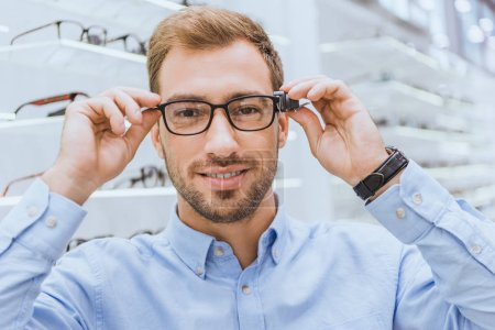 Photo for Portrait of young man choosing eyeglasses and looking at camera in optics - Royalty Free Image