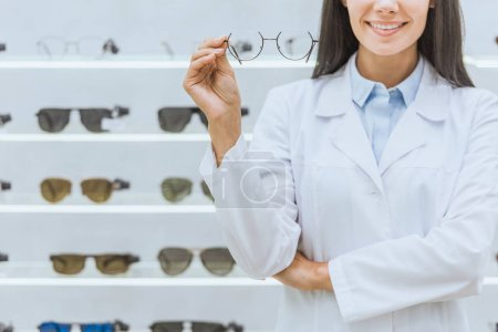 cropped view of smiling optometrist holding eyesight in optica