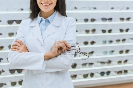 cropped view of professional doctor in white coat holding eyesight in optica