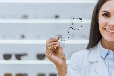 attractive smiling optometrist holding eyesight in optica