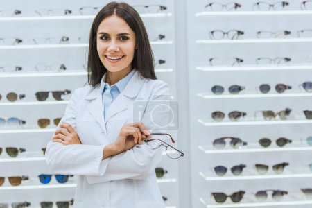 Photo for Professional smiling optician holding glasses near shelves in optica - Royalty Free Image
