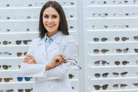 Photo pour Opticien souriant professionnel tenant des lunettes près des étagères en optica - image libre de droit