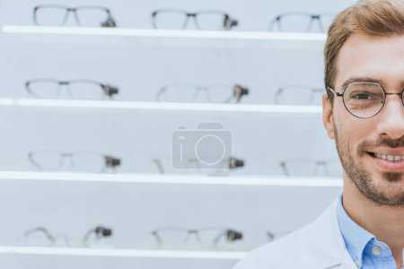professional handsome optician in glasses standing at shelves in optica
