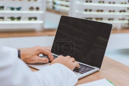 partial view of optician using laptop with blank screen in optica