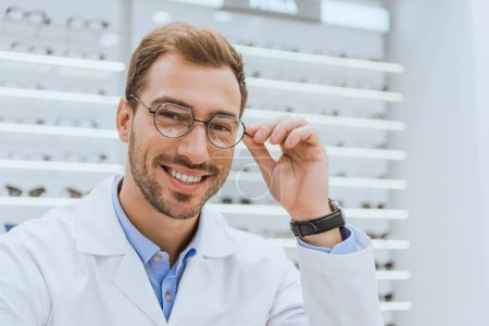 portrait of smiling professional optometrist in eyeglasses in optica