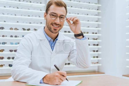Photo for Professional doctor in white coat writing diagnosis in optica - Royalty Free Image