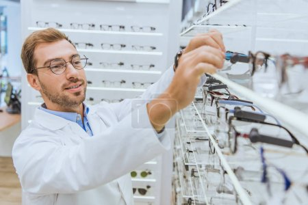 Photo for Professional male oculist in white coat taking glasses from shelves in optica - Royalty Free Image