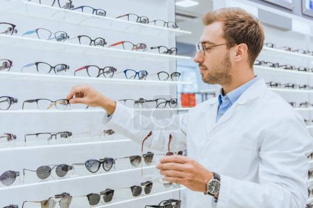 professional oculist taking eyeglasses from shelves in ophthalmic shop