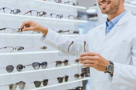 Photo pour Recadrée vue d'optométriste prenant lunettes de vue de la vente dans la boutique ophtalmique - image libre de droit