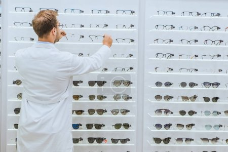 Photo for Back view of oculist in white coat taking glasses from shelves in ophthalmic shop - Royalty Free Image