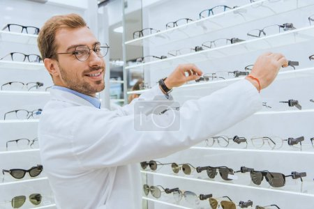 Photo for Smiling optician taking eyesight from shelves in ophthalmic shop - Royalty Free Image