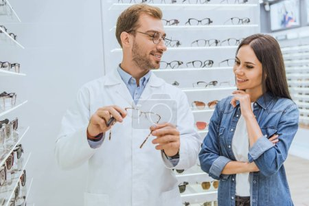male optometrist showing eyeglasses to smiling woman in optica