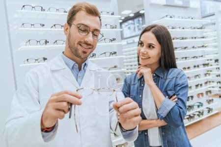 handsome male oculist showing eyeglasses to young woman in ophthalmic shop