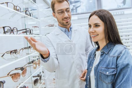 male oculist pointing by hand at shelves with eyeglasses to female in optics