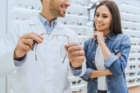 partial view of happy male oculist helping female to choose pair of eyeglasses in ophthalmic shop