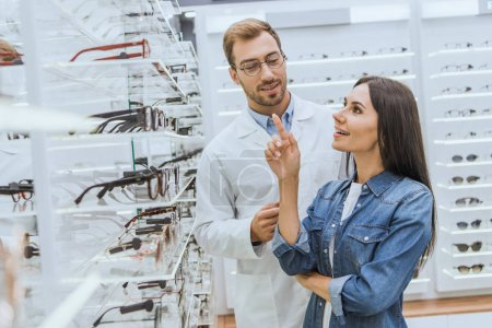 smiling woman pointing by finger at shelves with eyeglasses to male optometrist in optica