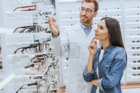 young male optometrist pointing by hand at shelves with eyeglasses to woman in optics